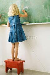 Little girl standing on stool  scribbling on blackboard  rear view