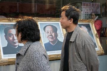 Peking  ein Paar laeuft am Mao-Portraet vorbei