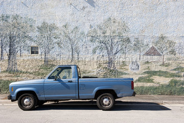 Pick-up truck parked beside wall with mural painted on it