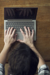 Man typing furiously on laptop computer