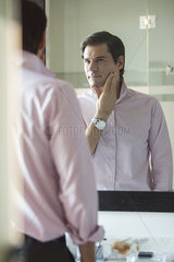 Man scrutinizing himself in mirror