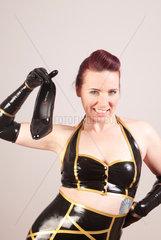 Frau im Latexkostuem haelt einen High Heel
