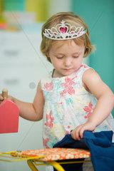 Little girl pretending to iron