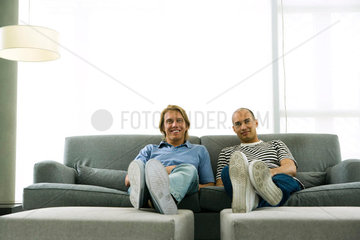 Two men sitting on sofa with feet up  smiling