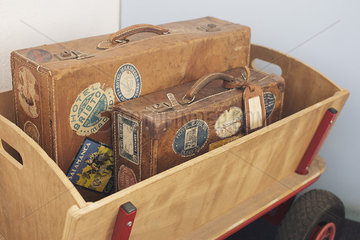 Child's wagon carrying antique suitcases
