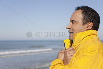 Mature man at the beach on a chilly day  eyes closed  portrait