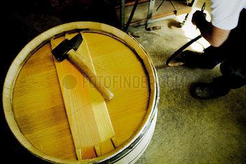 Hammer sitting on top of wine barrel