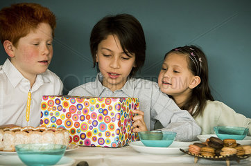Children looking at wrapped gift at birthday party
