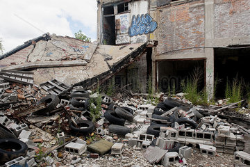 Trash and rubble heaped beside abandoned building in Detroit  Michigan  USA