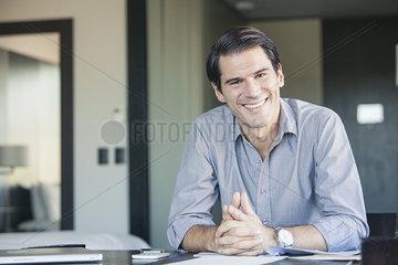 Businessman sitting at desk  smiling  portrait