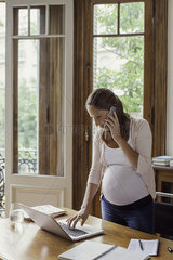 Woman using laptop computer and making phone call