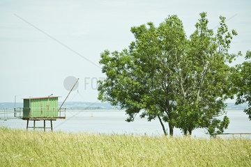 Fishing hut on stilts near water's edge