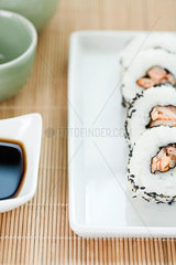 Cropped view of four pieces of maki sushi with soy sauce