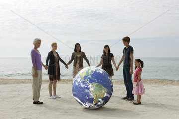 Ecology concept  group of people holding hands  standing around the planet earth