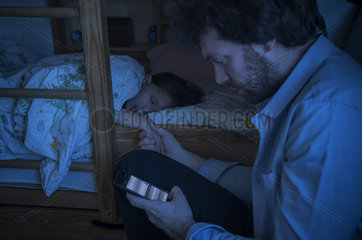 Father checking smartphone while comforting sick daughter
