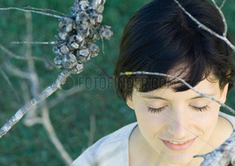 Woman standing amongst dry branches  head and shoulders