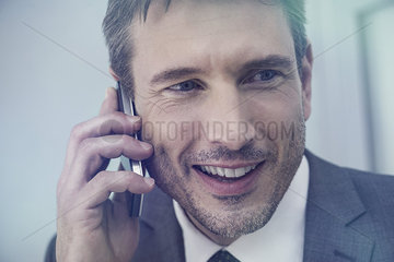 Businessman talking on cell phone  smiling cheerfully