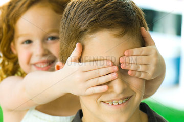 Girl holding hands over big brother's eyes  close-up