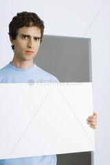 Man holding sign  furrowing brows at camera