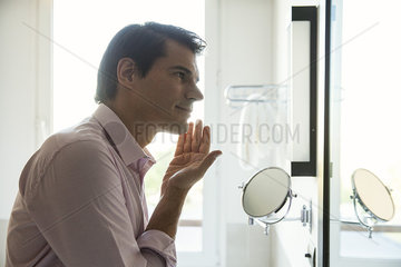 Man looking in mirror  applying moisurizer to face
