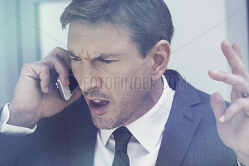 Businessman arguing on cell phone