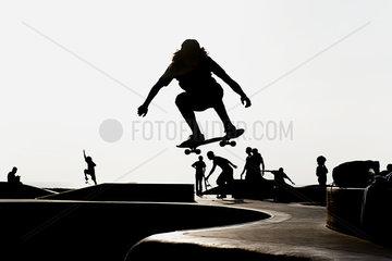 Skateboarder at skate park  silhouetted