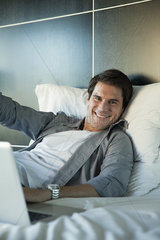 Man lying on bed  smiling cheerfully  portrait