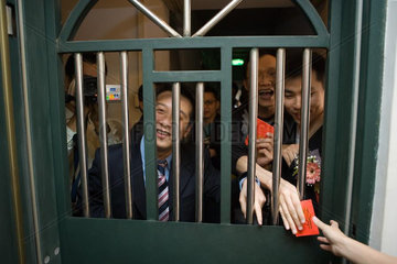 Chinese wedding door tradition  men looking through barred door  holding gift envelopes  laughing and smiling