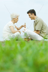 Senior woman with adult son  sitting in park sharing takeout food with chopsticks