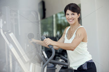 Woman exercising in fitness club  smiling cheerfully