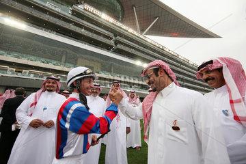 Dubai  Vereinigte Arabische Emirate  Jockey begruesst einen Mann im Fuehrring