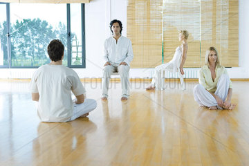 Four adults in various postures in wellness center