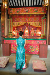 Young woman wearing traditional Chinese clothing  kneeling in front of shrine