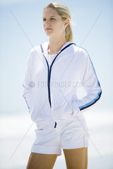 Young woman in active wear  standing on beach