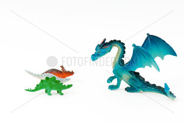 Toy dragon facing three small toy dinosaurs