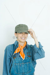 Teenage girl dressed in overalls  putting on hat  smiling at camera