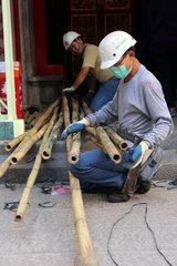 Hong Kong  China  Bauarbeiter kniet vor langen Bambusstaeben