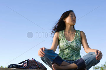 Woman sitting cross-legged outdoors on breezy day  eyes closed