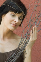 Woman holding dry branches  eyes closed