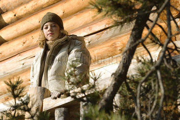 Teen girl standing on deck of log cabin  evergreen in foreground