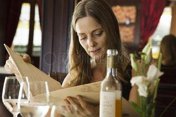 Mature woman looking at menu in restaurant