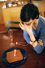 Woman sitting at table alone with anniversary cake  covering eyes