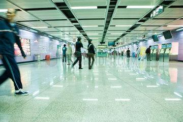 Commuters walking through subway corridor