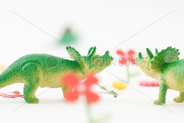 Toy triceratops face to face in artificial garden