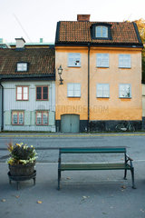 Sweden  Stockholm  bench and planter in front of rustic buildings