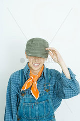 Teenage girl dressed in overalls  hat covering eyes  smiling