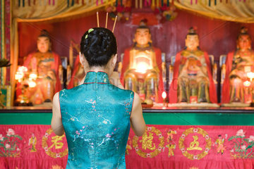 Young woman dressed in traditional Chinese clothing standing at shrine  rear view
