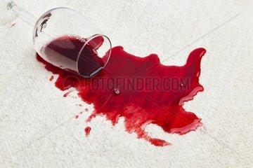 Roter Wein wird auf einem Teppich ausgeschuettet Umgeleertes Glas