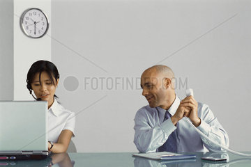 Office worker sitting at desk holding phone  covering receiver and speaking to female co-worker