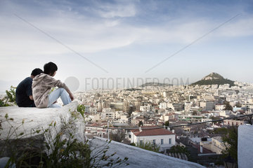 Tourists sitting on rock overlooking Athens  Greece and Mount Lycabettus